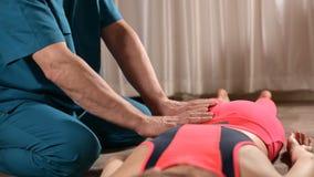 Мужской ручной висцеральный masseur терапевта обрабатывает молодого женского пациента Редактирование бедренной кости сток-видео