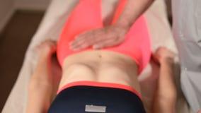 Мужской ручной висцеральный masseur терапевта обрабатывает молодого женского пациента Внешнее редактирование матки акции видеоматериалы