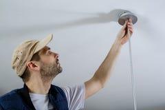 Мужской свет отладки электрика на потолке Стоковые Изображения