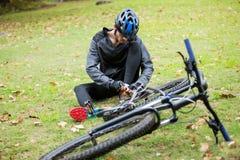 Мужской связывать велосипедиста шнурки в парке Стоковые Изображения RF