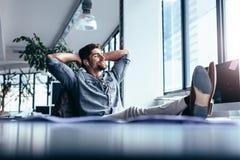 Мужской сидеть дизайнера ослабленный на его рабочем месте Стоковые Фотографии RF