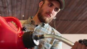 Мужской спортсмен заполняет его мотоцикл enduro с бензином сток-видео
