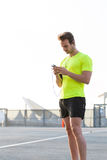 Мужской спортсмен использует мобильный телефон для того чтобы переключить музыку на списке игры во время разминки утра Стоковое Изображение