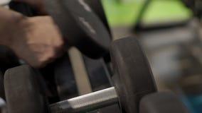 Мужской спортсмен принимает гантели в руках в современном спортзале внутри помещения акции видеоматериалы