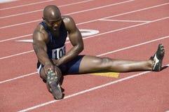 Мужской спортсмен протягивая на беговой дорожке Стоковые Фото