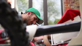 Мужской спортсмен ремонтируя его мотоцикл enduro видеоматериал