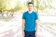 Мужской спортсмен усмехаясь пока стоящ на тропе в парке стоковая фотография rf