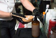Мужской стилизатор в перчатках подготавливая сливк для умирая контейнера волос, маску цвета для процедуры по обработки в салоне к стоковые изображения rf