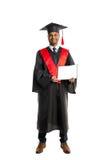 Мужской студент-выпускник афроамериканца в мантии и крышке Стоковое Фото