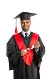 Мужской студент-выпускник афроамериканца в мантии и крышке Стоковое фото RF