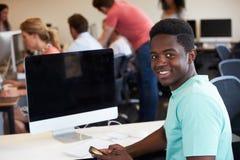 Мужской студент колледжа используя мобильный телефон в классе стоковая фотография