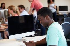Мужской студент колледжа используя мобильный телефон в классе стоковые фото
