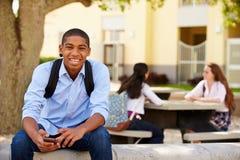 Мужской студент средней школы используя телефон на кампусе школы стоковые изображения