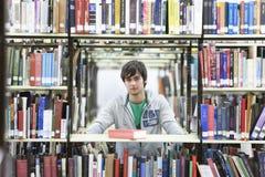 Мужской студент университета между книгами в библиотеке стоковое фото