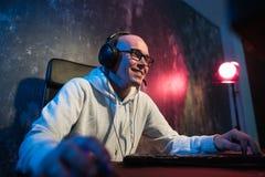 Мужской с капюшоном gamer играя Онлайн-игру на компьютере ПК стоковые изображения rf