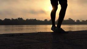 Мужской танец ног на впечатляющем речном береге на великолепном заходе солнца в Slo-Mo видеоматериал