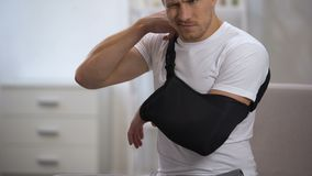 Мужской терпеливый регулируя слинг руки в свойственном положении, реабилитации после травмы видеоматериал