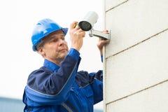 Мужской техник исправляя камера CCTV на стене стоковые фото