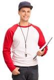 Мужской тренер бейсбола держа доску сзажимом для бумаги Стоковые Изображения