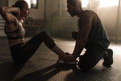 Мужской тренер помогая женщине в делать сидеть-поднимает на спортзале стоковое фото