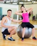 Мужской тренер при женщина делая хрусты на шарике Стоковые Фото