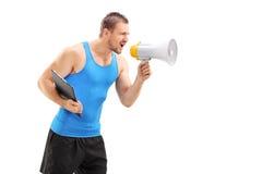 Мужской тренер фитнеса крича через мегафон Стоковое фото RF