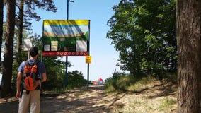 Мужской туристский задний взгляд с рюкзаком смотря стойку информации на пляже Карта области и предупредительных знаков акции видеоматериалы