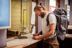 Мужской турист покупает билет на кассе конечной станции стоковая фотография rf