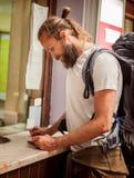 Мужской турист покупает билет на кассе конечной станции стоковые фото