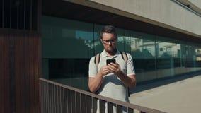 Мужской турист соединяет его смартфон для того чтобы освободить сеть wifi здания видеоматериал