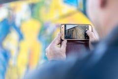 Мужской турист фотографирует известное художественное произведение на Берлине e Стоковые Изображения RF