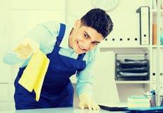 Мужской уборщик 25-30 лет очищает пыль от стола Стоковая Фотография RF