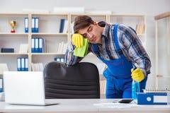 Мужской уборщик работая в офисе стоковое изображение