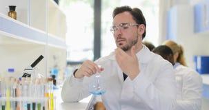 Мужской ученый анализируя запах жидкости в склянке работая в пальто носки химической лаборатории белом и защитных стеклах видеоматериал