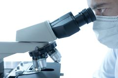 Мужской ученый делая микроскоп для образцов теста химии, рассматривая Лабораторное оборудование и эксперименты по науки стоковая фотография rf