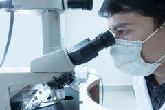 Мужской ученый делая микроскоп стоковая фотография