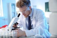 Мужской ученый используя современный микроскоп в лаборатории химии стоковые фотографии rf