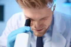 Мужской ученый используя современный микроскоп в лаборатории химии стоковые фото