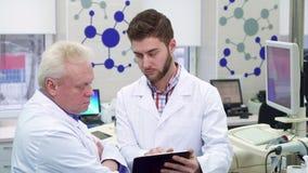 Мужской ученый показывает что-то на его таблетке к его сотруднику на лаборатории акции видеоматериалы