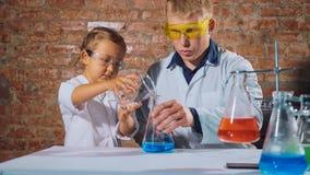 Мужской ученый с маленькой школьницей проводит химический эксперимент совместно стоковые изображения rf