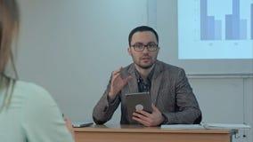 Мужской учитель держа цифровую таблетку сидя перед студентами и беседой к камере Стоковые Фото