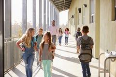 Мужской учитель и зрачки идя на кампус школы стоковая фотография rf