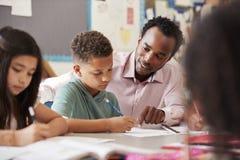 Мужской учитель работая с мальчиком начальной школы на его столе стоковые фотографии rf