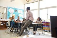 Мужской учитель с детьми начальной школы в школьном классе стоковое фото rf