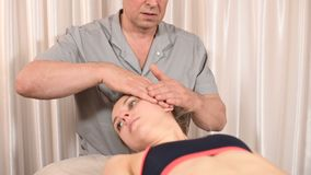 Мужской физиотерапевт делает здоровьем ручную процедуру для пациента маленькой девочки Osteopathy и нетрадиционное акции видеоматериалы