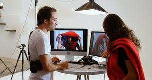 Мужской фотограф показывая фото к женской модели на компьютере 4k сток-видео