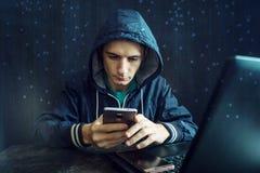 Мужской хакер использует мобильный телефон для того чтобы прорубить систему концепция злодеяния кибер и рубить электронных устрой стоковое фото rf