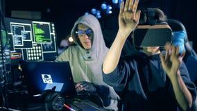 Мужской хакер и его женский коллега в VR-стеклах работают видеоматериал