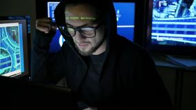 Мужской хакер работая на компьютере пока зеленые кодовые знаки отражают на стороне в темной комнате офиса, шпионаж интернета, акции видеоматериалы