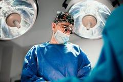Мужской хирург выполняя хирургию в театре больницы работая стоковая фотография